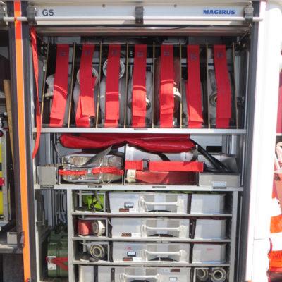 Gerätefach 5: u.a. 7 B-Schläuche gerollt, mobiler Rauchverschluss,  4 Schlauchtragekörbe mit C-Schläuchen, Verteiler. Zusätzlich zu sehen: 2 Abgänge der Fahrzeugpumpe