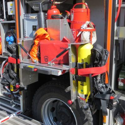 Ausgezogene Halterung für Pressluftatemschutzgeräte, auf der Rückseite sind Feuerlöscher und Kübelspritze verlastet