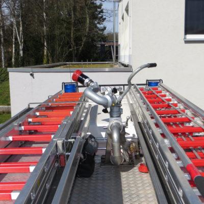Dachansicht: links 4-teilige Steckleiter, rechts 3-teilige Schiebeleiter, mitte montierter Wasserwerfer